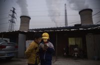 BEIJING, CHINA - NOVEMBER 27: Chinese boys look at their smartphone in front of their house next to a coal fired power plant on November 27, 2015 on the outskirts of Beijing, China.  China's government has set 2030 as a deadline for the country to reach its peak for emissions of carbon dioxide, what scientists and environmentalists cite as the primary cause of climate change. At an upcoming conference in Paris, the governments of 196 countries will meet to set targets on reducing carbon emissions in an attempt to forge a new global agreement on climate change. (Photo by Kevin Frayer/Getty Images)